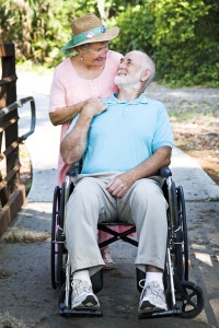 Disabled senior man in wheelchair with his loving wife taking care of him.