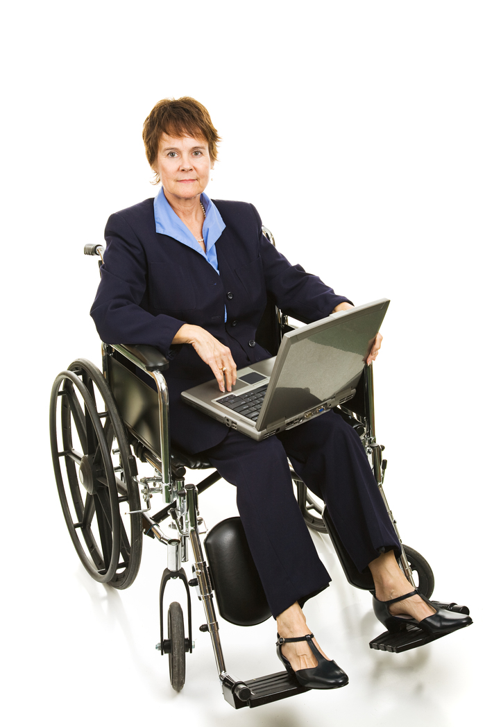 Serious buisinesswoman in a wheelchair working on her laptop computer.  Isolated on white.